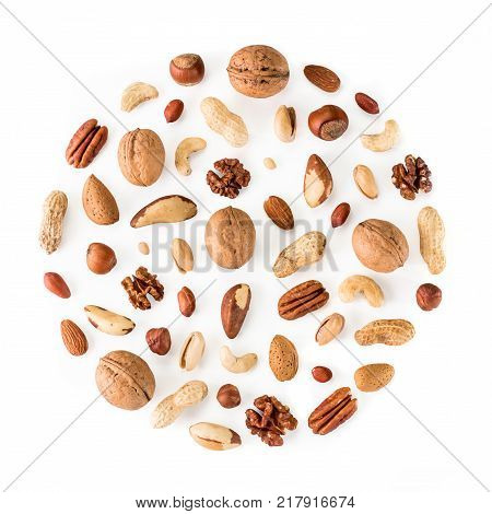 Pattern of nuts in circle form. Various nuts isolated on white. pecan, macadamia, brazil nut, walnut, almonds, hazelnuts, pistachios, cashews, peanuts, pine nuts. Top view or flat-lay. Copy space