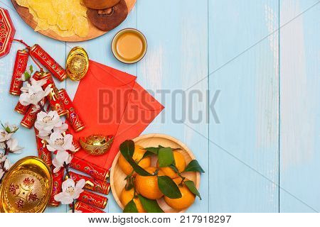 Lunar new year.Firecrackers and Chinese gold ingots and Traditional Red envelopes and decoration with Fresh oranges on wooden background