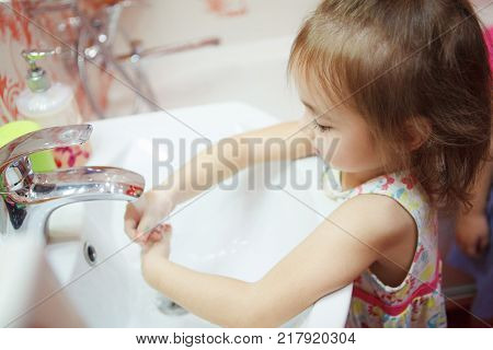 Kid with fair hair, wearing t-shirt and thoroughly washing hands in bathroom with water and soap, following rules and maintain hygiene, healthy lifestyle of child