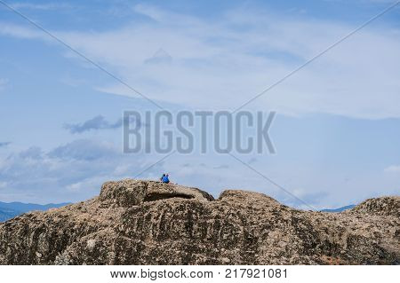 Female and man on the edge of the rock look on the monasteries of Meteora. Meteora in Greece in Thessaly at the early morning