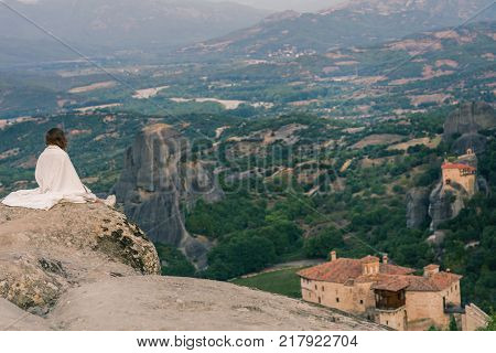Alone female in the white plaid on the edge of the rock look on the monasteries of Meteora. Female on the rock and monasteries of Meteora in Greece in Thessaly at the early morning