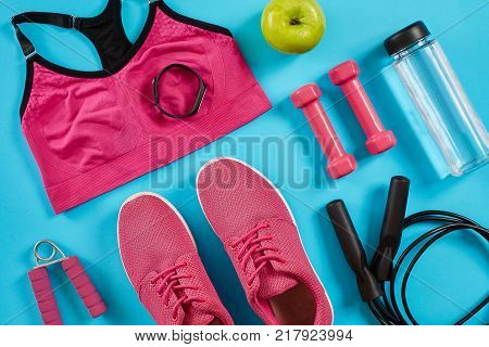 Athlete's set with female clothing, dumbbells and bottle of water on bright blue background. Top view. Copy space. Still life. Flat lay