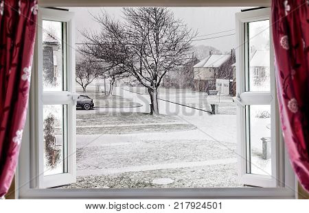 View through open window onto a beautiful winter snow street scene in rural England. Red curtains hang in front of the modern double glazed window