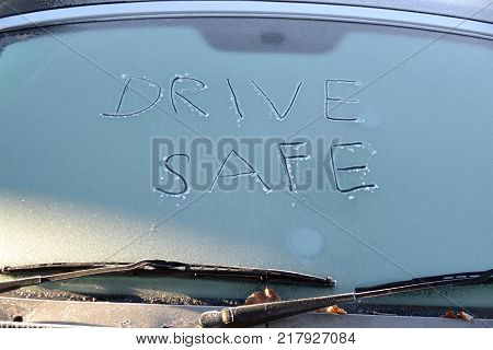 Drive safe written on the ice on a windscreen of a car during winter