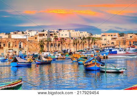 Marsaxlokk village port of Malta illuminate by sunset light, European travel in beautiful place