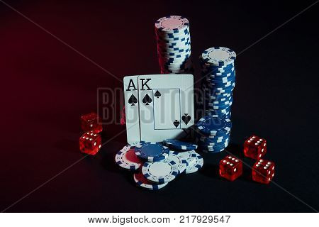 Stack of chips and two cards on dark background - poker game concept. Still life. Copy space. Poker Online. Cards - Ace and King