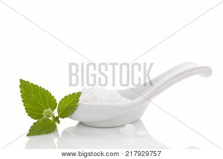 Artificial sweetener pills in white spoon and aztec sweet herb isolated on white background. Sugar substitute. Natural and artificial sweetener.