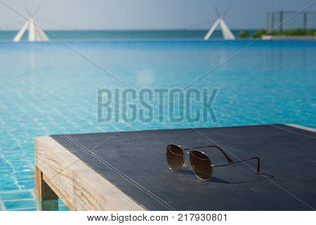 Sunglasses on daybed with swimming pool and seascape view in the background. (Selective focus)