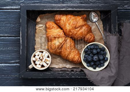 Croissants with blueberries and coffee on a wooden black tray. Top view, rustic style