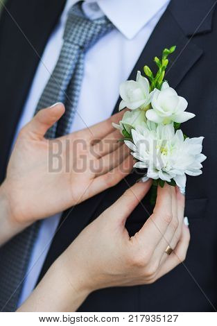 Closeup of beautiful floral corsage ready to be pined at blue suit of man. Vertical color photography.