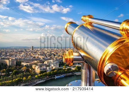Monocular telescope and panoramic views of Paris in sunny day with survey site of Eiffel Tower. Vacation in Paris