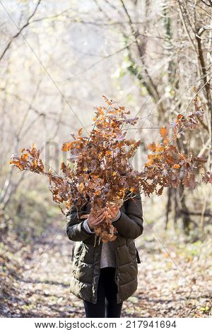 girl in the nature holding yule log branches covering her face