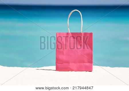 Shopping bag on sand against turquoise caribbean sea water. Tropical celebration on beach