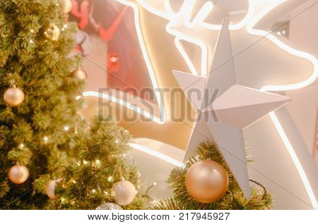 Decorating Christmas tree close up. Decoration bulb, green fir tree, golden x-mas toys and lights. Use for Christmas and New years celebration background