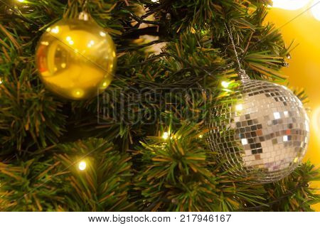 Decorating Christmas tree close up. Decoration bulb, green fir tree, golden x-mas toys and lights.