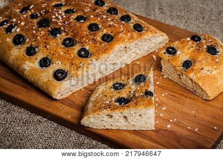 Delicious homemade focaccia. Traditional Italian bread with olives and sea salt
