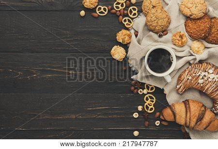 French croissants and coffee background. Tasty french breakfast with variety of homemade cookies, nuts and buns. Mockup for sweet pasrty recipe, top view, copy space