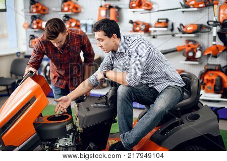 A consultant in a garden tools store shows a customer a lawn mower. There are many tools for gardening here. A young family came to choose their equipment.