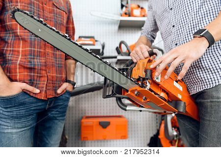 The seller in the store shows the customers a chainsaw. A young couple came to the garden tools store to buy equipment for gardening.