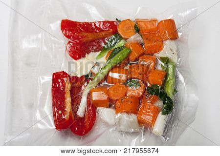 sous vide bags with mixed vegetables on white