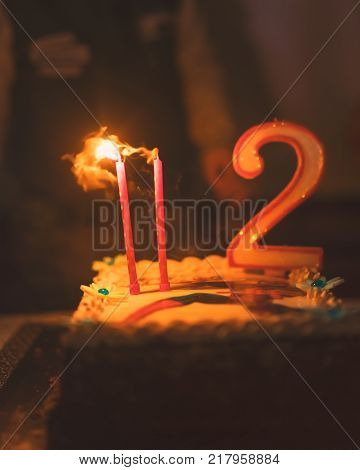Happy birthday cake with two candles low depht of focus for dreaming atmosphereused split toning.