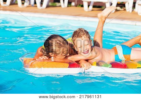 Little children playing and having fun in swimming pool with air mattress. Kids playing in water. Swimming concept. Boy and girl swim in resort pool during summer vacations