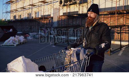 Homeless person pushing his shopping cart down the street