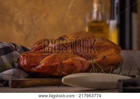 Horizontal photo with big piece of smoked pork meat with bone placed on cutting board. Blue towel chopper fork bowls and rosemary are around with wine and oil in background with vintage wall.