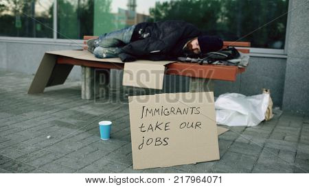 Homeless and jobless european man with cardboard sign sleep on bench at the city street because of immigrants crisis