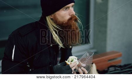 Homeless young man eating sandwich and drinking alcohol from paper bag on bench at city street