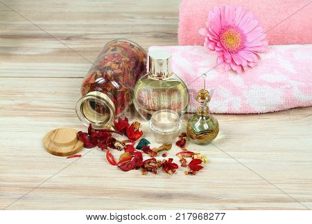 Spa concept with candles and flower. Aromatherapy treatment aromatic herbs oil perfume and body cream on wooden background
