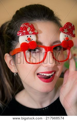 Portrait of smiling and sexy young woman with Christmas snowman glasses sticking tongue out