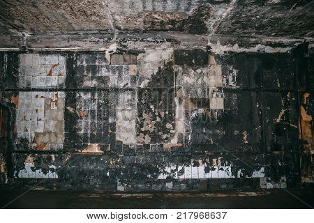 Burned by fire interior of old building. Charred ash walls, dark toned