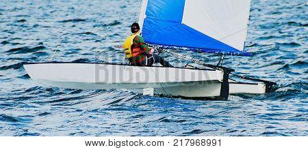 Young female High School student sailing racing a catamaran in the Australian championships at Lake Mac quarie Australia.