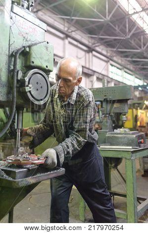 Tyumen, Russia - September 7, 2010: JSC Tyumenskie Motorostroiteli Plant on production and repair of aviation engines. Milling-machine operator works at the machine
