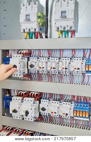 Man switch switch protection engine to check in the electrical Cabinet. In the electrical control Cabinet on a mounting plate fixed circuit-breakers motor protection relay. poster