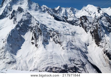 Snow covered mountains with glacier at cold sun day. Caucasus Mountains region Dombay in winter.