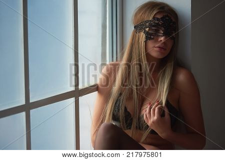 Sexy woman in lace mask. Attractive girl near the window.