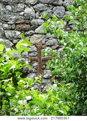 Christian cross on the wall of the house of the ancient city of Olympos. Turkey