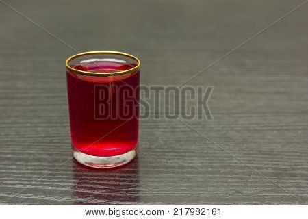 A glass of red sweet cherry liqueur on the table.