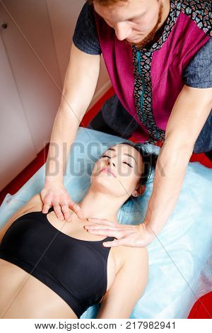 young handsome male massage therapist doing relaxing classical massage in a girls oven lying on massage table in beauty studio for getting Beautiful body