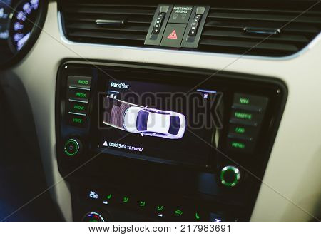 STRASBOURG, FRANCE - NOV 12, 2016: Generic parkpilot parktronic electronic aid system sensors with maneuver of the car on the screen and text: Look safe to move?