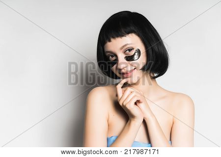 attractive young girl with black hair, under the eyes of black silicone patches, looks at the camera