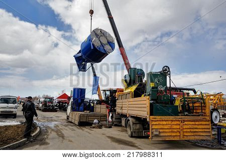 Tyumen, Russia - April 04. 2014: IV Tyumen specialized exhibition Agricultural Machinery and Equipment. Unloading loading of the equipment of participants of agricultural exhibition