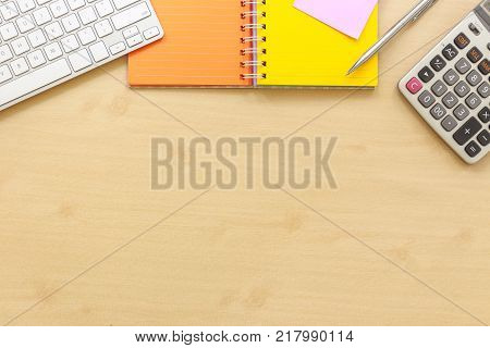 Top View Of Office Desk With Most Blank Space. Stationery Keyboard Colorful Paper Book Calculator An