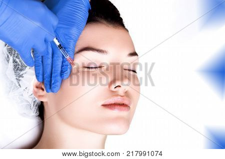 beautiful and well-groomed girl is given injections of youth, wrinkle smoothing, hyaluronic acid, facial skin care