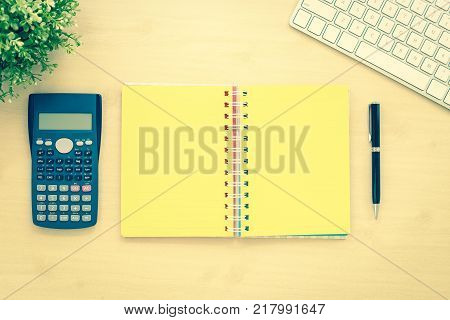 Above view of open book with yellow blank pages calculator keyboard plants and black pen on office table background. Resolution goals and planning concepts. Sepia tone vintage and retro styles.