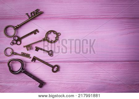 Vintage keys collection. Key Love and key Dream on the pink wooden background. Top view, free space