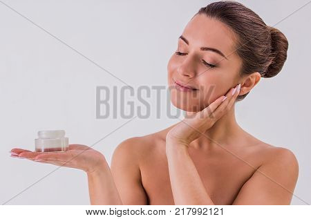 Confident in her beauty. Portrait of beautiful shirtless woman holding in one hand cream jar and touching face with another hand isolated on white background. Skin treatment and beauty concepts