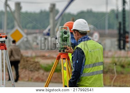 Tobolsk, Russia - July 15. 2016: Sibur company. Construction of plant on processing of hydrocarbons. Surveyor builder worker with theodolite transit equipment at construction site outdoors during surveying work